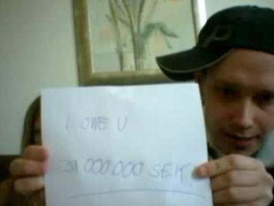 """Peter Sunde trzyma kartkę z napisem """"I Owe U 31 million SEK"""". Zdjęcie z webcastu po ogłoszeniu wyroku sądowego."""