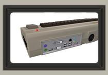 """Wejścia z tyłu komputera (m.in. USB i SATA), a tle: klasyczna dioda C-64, która służy teraz jako przycisk """"POWER""""."""