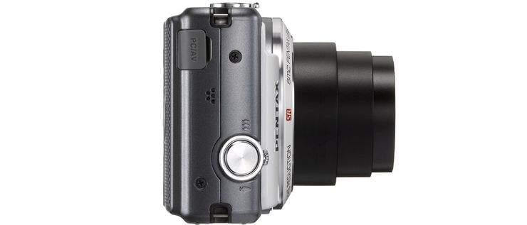 Z boku aparatu Optio VS20 znajduje się dodatkowy spust migawki oraz dźwignia zooma