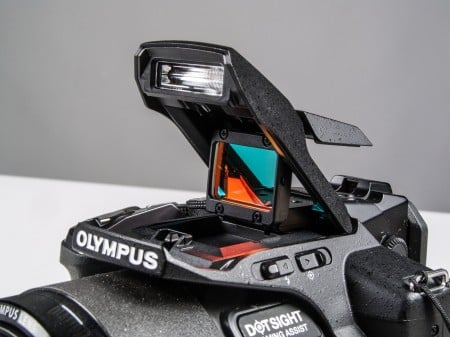 Kolimatorowy celownik ramkowy, zastosowany w modelu Olympus SP-100EE. Więcej informacji na temat tego ciekawego rozwiązania znajdziesz przy opisie aparatu.